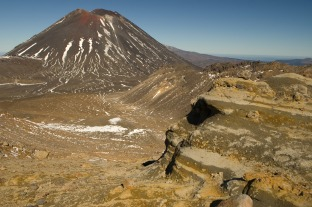 Layered, hydrothermally altered volcanic deposits dot the foreground, Mt. Ngarahoe visible in the background from Mt. Tongariro