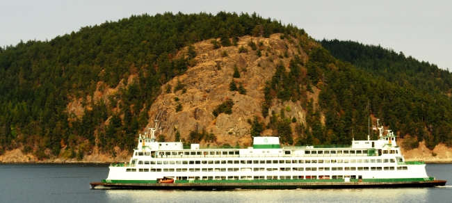 A ferry passes rock outcrops in the San Juan Islands