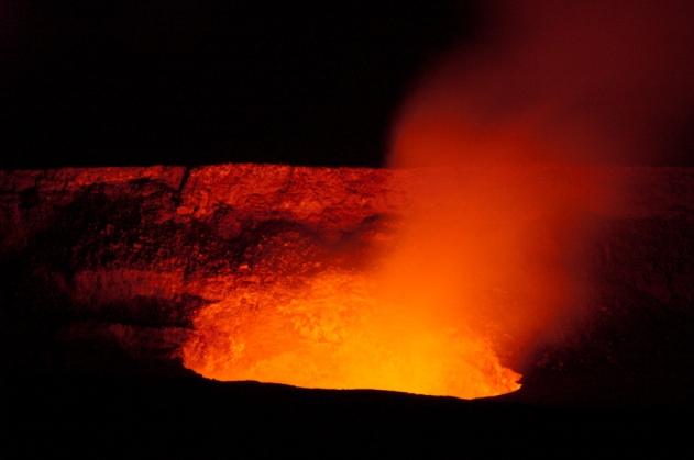 A lava lake just below the surface illuminates the wall of Halemaumau Crater
