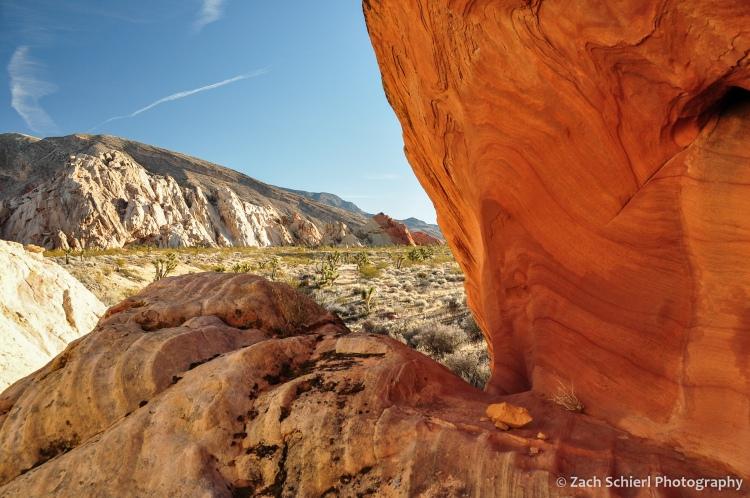 A notch in a sandstone boulder frames a view of a desert landscape.
