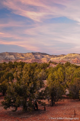 Pink clouds and a band of pink rocky cliffs at sunset