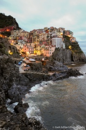 Colorful buildings of Manarola line the waterfront at dusk.