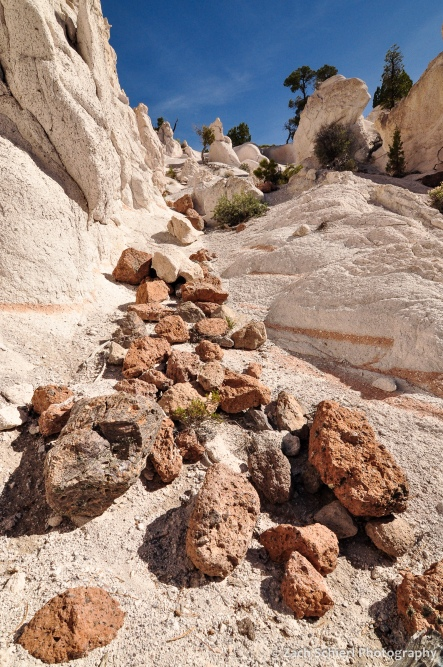 Pink and brown boulders lie strewn in a chute of white tuff