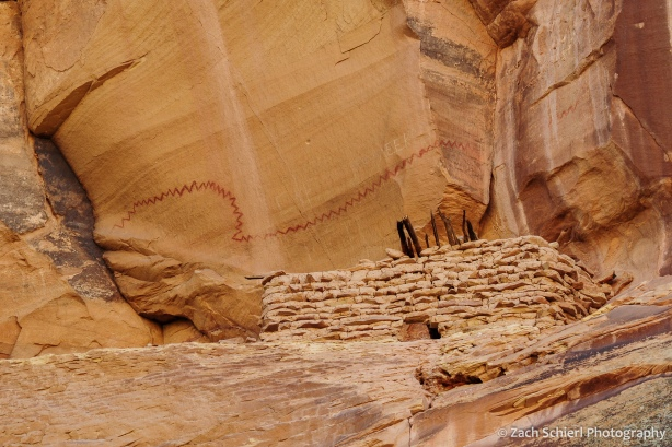 Cliff dwelling in a cliff alcove surrounded by pictographs.
