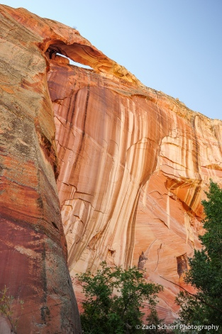 A small arch sits at the top of a colorful sandstone cliff.