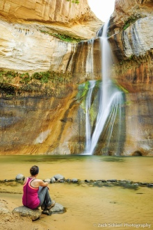Sitting on a rock looking at a waterfalls tumbling from the sandstone cliffs.