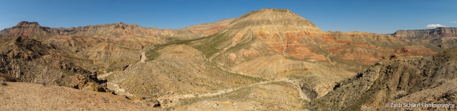 A desert scene with colorful cliffs and sparse vegetation.
