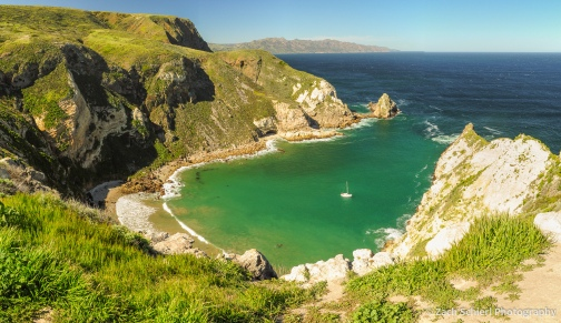 A small ocean inlet with blue-green water along a rugged coastline