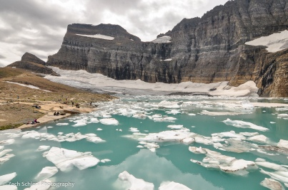 Gray cliffs of igneous and sedimentary rock tower over a aquamarine lake filled with icebergs