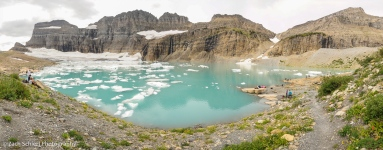 Cliffs of rock surround several glaciers and an azure-blue lake containing numerous icebergs.