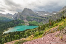 Dark clouds loom over a range of mountains and an azure-blue alpine lake