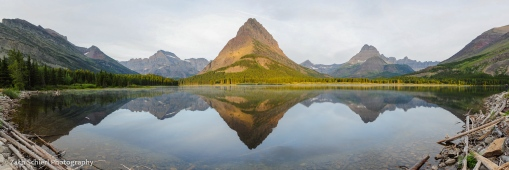 A series of sharp mountain peaks are reflected in a tranquil lake at sunrise.