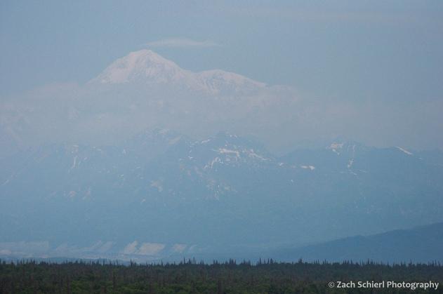 View of snowy peak through a layer of smoke