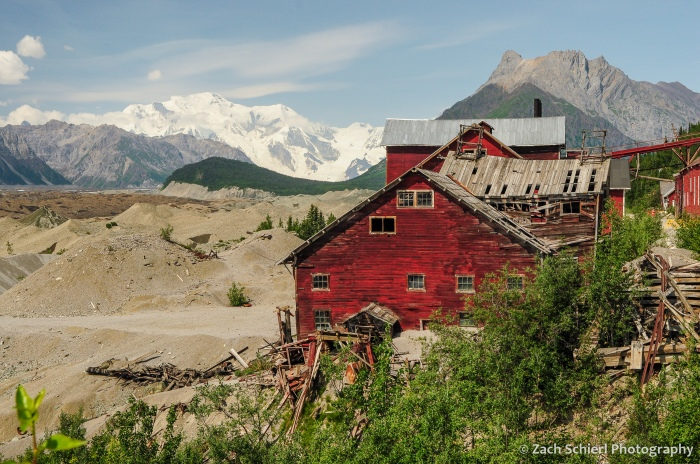Wooden buildings cling to a slope with glacier covered mountains in the background