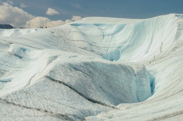 Several people stand on the crest of a white and blue mass of glacial ice