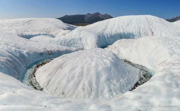 A channel of water flowing across a white glacier carves a tight bend in the ice