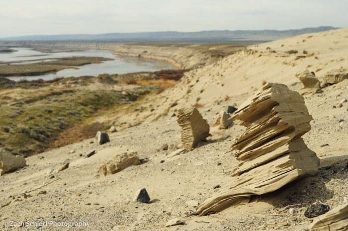 Rocks sculpted by the wind sit on the ground with a view of a large river in the background
