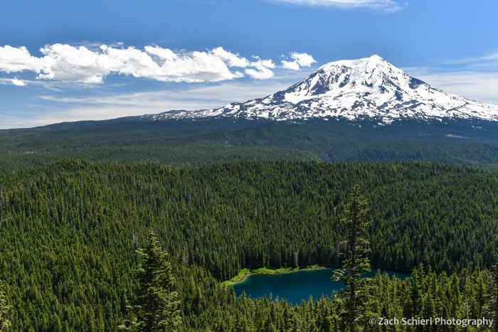 A tall mountain capped with snow and ice is surrounded by dense, dark green forests and a dark blue lake.