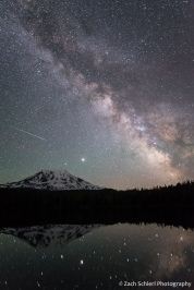The night sky including the Milky Way and the streak of a meteor is seen over a tall mountain peak.