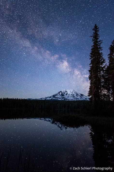 A dark blue twilight sky is bisected by the glow of the Milky Way, and reflected in a tranquil pond.