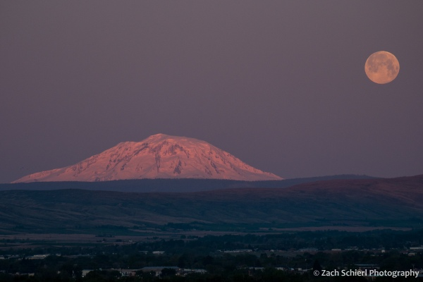Pink morning light on a snow-capped mountain peak with a full moon setting in the background.