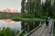 Orange sunset light on a tall, snow-capped mountain peak is reflected in a foreground pond.