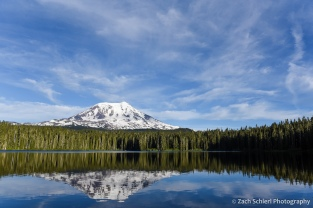Volcanic cone and wispy clouds reflected in a tranquil mountain lake.