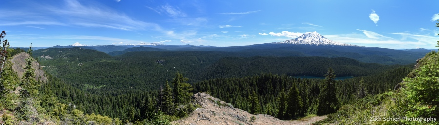 Panorama of forested landscape dotted by tall volcanic peaks.