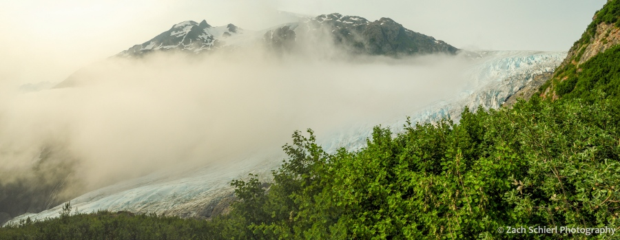 A valley containing a glacier is partially obscure by a bank of clouds