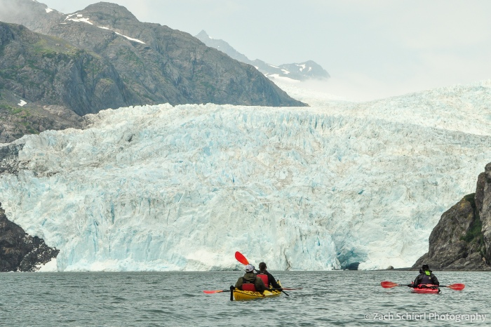 Two kayakers approach a large glacier