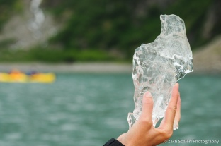 A hand holds a small piece of ice that has broken off of a glacier