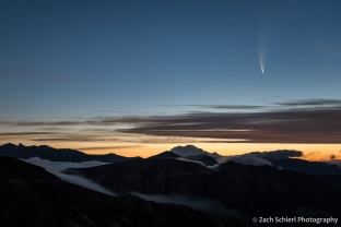 A comet and its tail appears in the pre-dawn sky with a mountain range and valley fog in the foreground