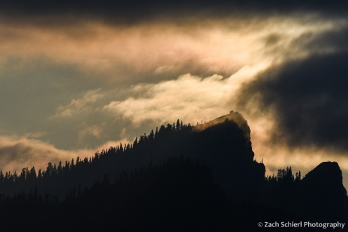 The setting sun casts a pink glow on low clouds above a rocky pinnacle with a lookout tower.