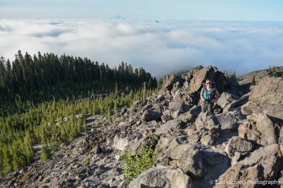 A hiker scrambles up a rocky slope with a forest and low-lying clouds in the background