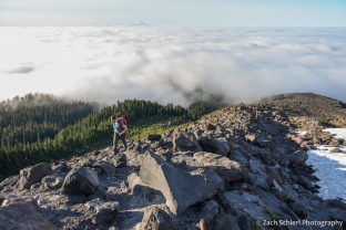 A hiker walks along a rocky ridge with clouds and a distant volcanic peak in the backgrounde background