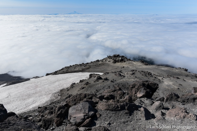 Dark, jagged volcanic rocks on the slopes of Mt. St. Helens with clouds far below