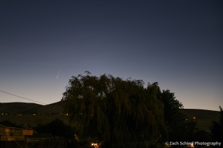 A bright comet appears just over the horizon in the pre-dawn sky