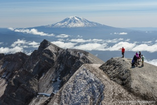 View of rocky and snowy ridgeline with volcanic peak in the background