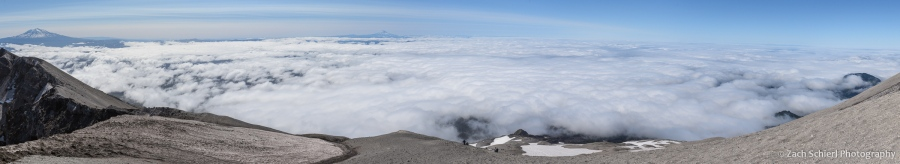 Panorama showing a variety of distant mountains and a low cloud layer
