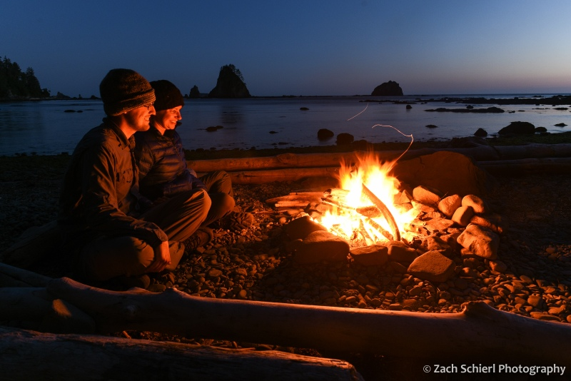 Two people sit on a log illuminated by the glow of a campfire.