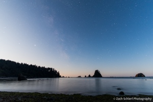 The Milky Way is just barely visible in the sky over the coastline