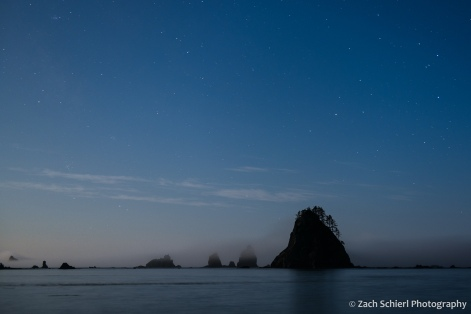 Several rocky islands sit in a bay with stars in the sky overhead.