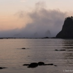 Clouds and mist surround several large rocky islands sitting in a calm bay