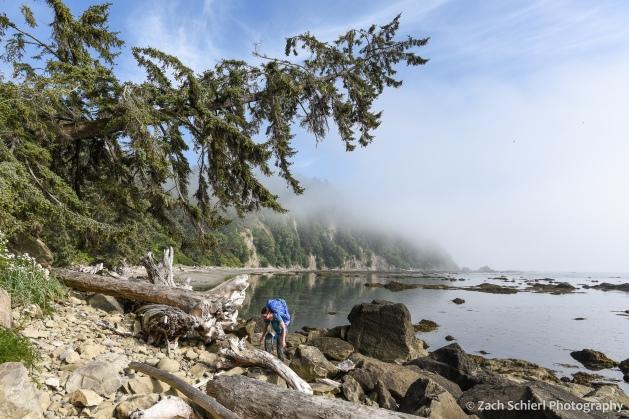 A hiker with a large backpack navigates a pile of boulders along a coastline.