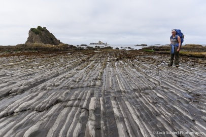 Alternating bands of dark and light colored rock stretch to the horizon along the coastline.