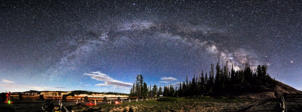The Milky Way stretches from horizon to horizon with some clouds hovering near the horizon.