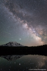 A photograph of the Milky Way galaxy hovering over a tall volcanic peak.