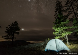 A softly lit tent at the edge of a forest is seen with the night sky partially obscured by clouds overhead.