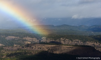 A bright rainbow intersects a series of forested plateaus