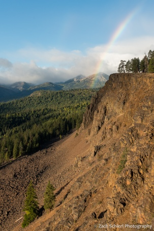A mountain scene with low clouds, a rainbow, and red-brown cliffs of crumbly rock